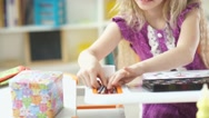 Girl draws. Beautiful blond girl takes the crayons from the box Stock Footage