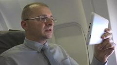 Confident Business Man Talk Digital Tablet Video Call Conversation Plane Travel Stock Footage