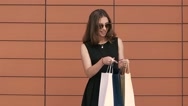 Pretty young shopping woman views her purchases in the shopping bags. Stock Footage