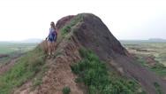 Young Woman Trekking along Mound Ridge Stock Footage