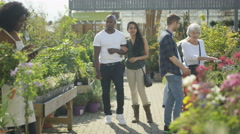 4K Customers shopping in plant nursery & worker with tablet computer Stock Footage
