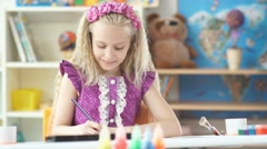Righty girl carefully paints using colored pencils Stock Footage