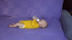 Baby with yellow romper drink milk bottle on couch. Baby care. 4K Stock Footage