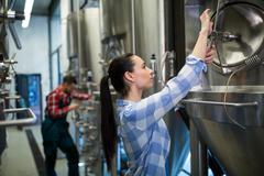 Female maintenance worker examining brewery machine at brewery Kuvituskuvat