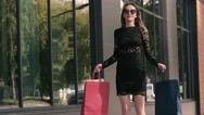 Pretty young woman in black dress jumps in excitement with shopping bags Stock Footage