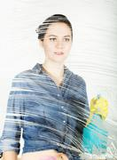 Young housewife washed window with a spray, cloth and detergent. Large glass in Stock Photos