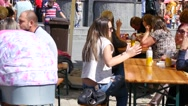 People relax eat and drink beer on a street food festival sitting at tables Stock Footage