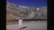 1958: stout woman in pink dress strides away towards lake with hills  Stock Footage
