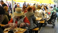 Senior old age people sit at tables eating fast dishes at street food festival Stock Footage