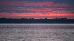 Birds fly on background of majestic sky over water at dawn Stock Footage
