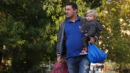 Man father with two kids walking down the park alley Stock Footage