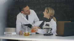 4K Scientists working in lab writing chemistry & maths formulas on blackboard Stock Footage