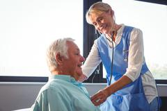 Nurse using stethoscope to take care of a senior man in a retirement home Kuvituskuvat