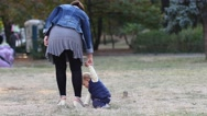 Mother walking with toddler child boy hold him by hand outdoors on park lawn Stock Footage