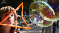 Woman blow a beautiful colored soap bubbles outdoors in public park slow motion Stock Footage