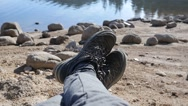 Man tourist hiker relax by a lake water - lying legs sneakers camera view Stock Footage