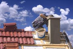 Roofer builder worker repairing a chimney stack on a roof house Stock Photos