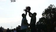 Strong basketball team men play outdoors street game sun silhouettes throw ball Stock Footage