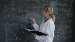 4K Portrait smiling woman in white coat writing math formulas on blackboard Arkistovideo
