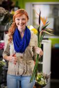 Portrait of smiling female florist trimming flower stem at flower shop Stock Photos