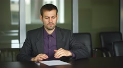 Businessman's hand signing document. Man signs paper beside window. New Stock Footage