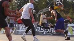 Strong basketball team men play outdoors street game sun silhouettes slow Stock Footage