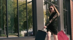 Lovely young shopping woman holds colorful shopping bags walks in the city Stock Footage