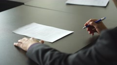 Notary signing papers near window. Read everything carefully. Time to make Stock Footage