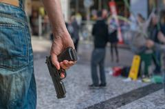 Gun control concept. Armed man - attacker holds pistol in hand in public plac Stock Photos