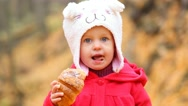 Small child eating croissant outside on cold autumn day Stock Footage