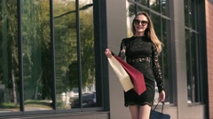 Beautiful fair-skinned young lady in black dress moves shopping bags Stock Footage