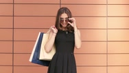 Portrait of lovely woman walking in and stopping to look from the sunglasses Stock Footage
