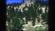 1958: a beautiful blue sky above a beautiful rugged mountain peak as seen pine Stock Footage