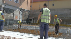 Construction workers installing armature at building site by Sheyno. Stock Footage
