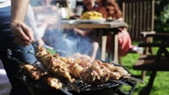 Man cooking meat on barbecue grill at summer party Stock Footage
