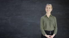 4K Woman talking directly to camera & pointing to blank chalkboard background Stock Footage