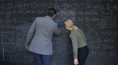 4K Time lapse man & woman cleaning off chalkboard to leave blank copy space Stock Footage