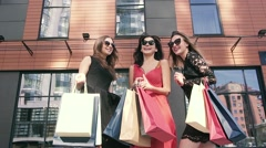 Group of cheerful women enjoying their successful shopping day in the city Stock Footage