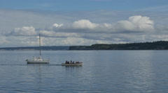 Seven people in small motorboat pass anchored sailboat in Puget Sound Stock Footage