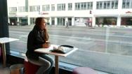 Young woman enjoy hot drink, sit in cafe near big glass window, Helsinki Stock Footage