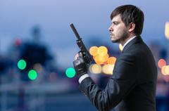 Secret agent or spy holds pistol in hand at dusk. Kuvituskuvat