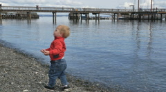 Cute boy throws rocks in water pier in background Stock Footage