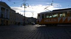 Car and tram pass by Senate Square, high contrast evening sunlight Stock Footage