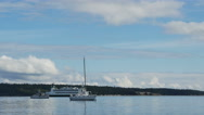 Boat and ferry pass anchored sailboat in Puget Sound Stock Footage