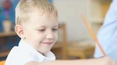 Portrait of a cute boy with blond hair. Boy draws using paints Stock Footage