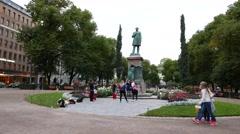 Young people gather near monument at Esplanadi park, evening Helsinki Stock Footage