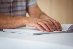 Senior man using braille to read in a retirement home Stock Photos