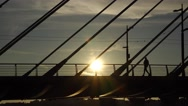 Boy come along cable stayed bridge handrails, silhouette view, bright sun spot Stock Footage