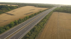 Highway traffic in rural countryside setting, fields of wheat. Aerial view Stock Footage