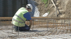 Construction worker placement reinforcing mesh at building site by Sheyno. Stock Footage